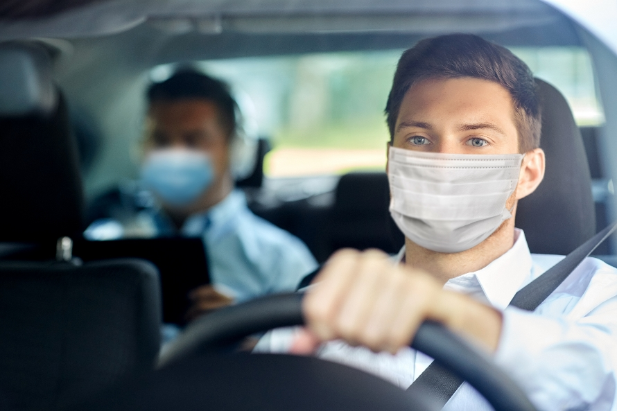 Mann mit Atemschutz am Steuer