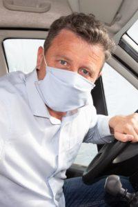 Mann mit Schutzmaske am Steuer