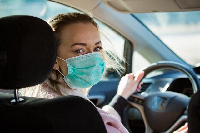 Frau mit Schutzmaske im Auto